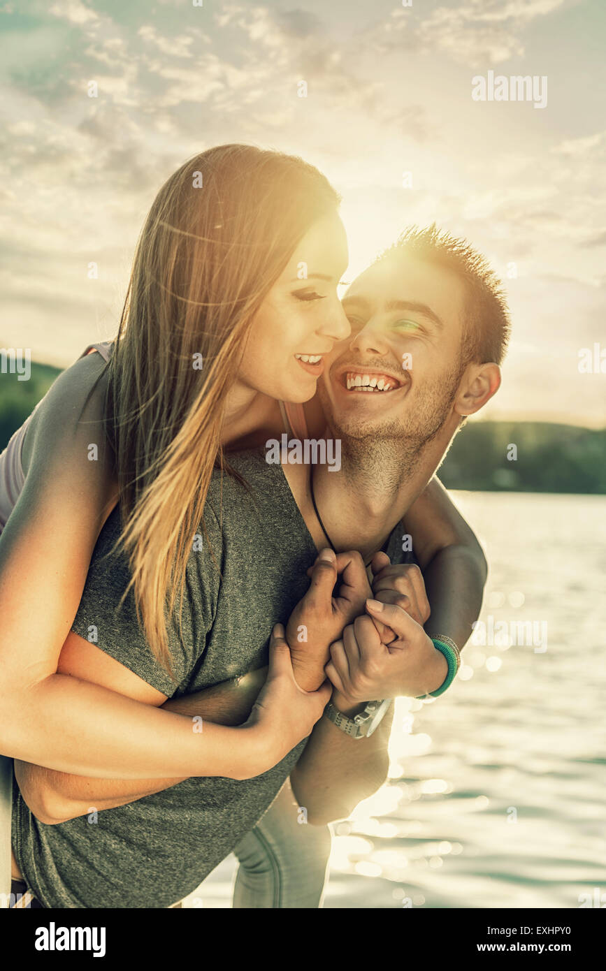Couple in love embracing at the lake, sun flare - Stock Image