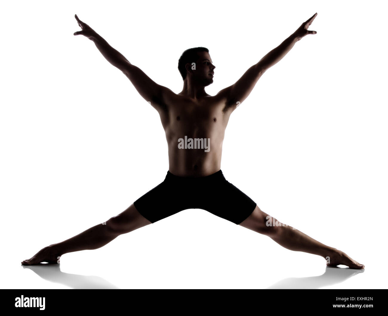 Silhouette of an muscular adult male modern contemporary ballet style dancer. Dancer is wearing black ski pants - Stock Image