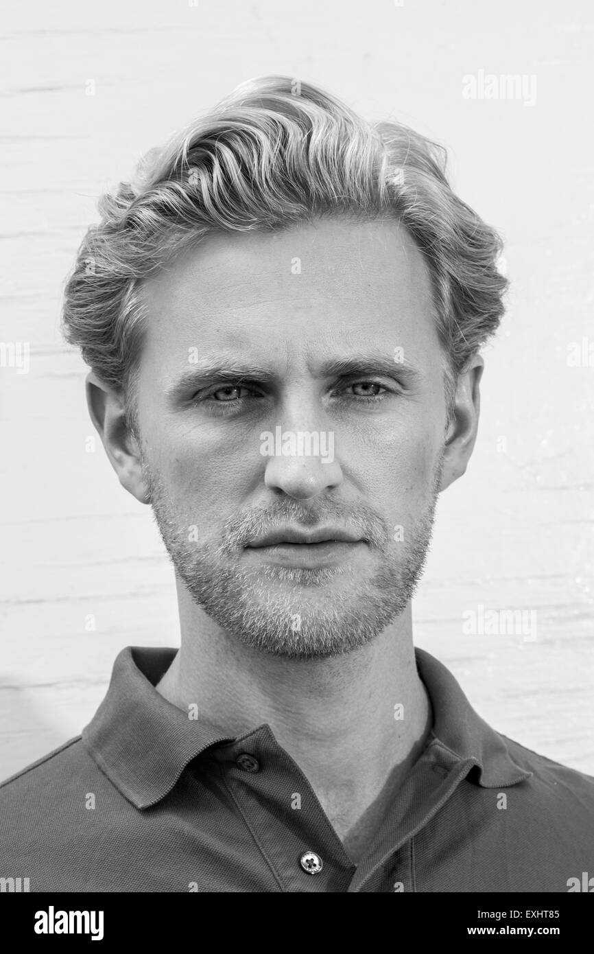 Headshot of a blonde man with face stubble looking moody wearing a polo shirt in black & white. - Stock Image