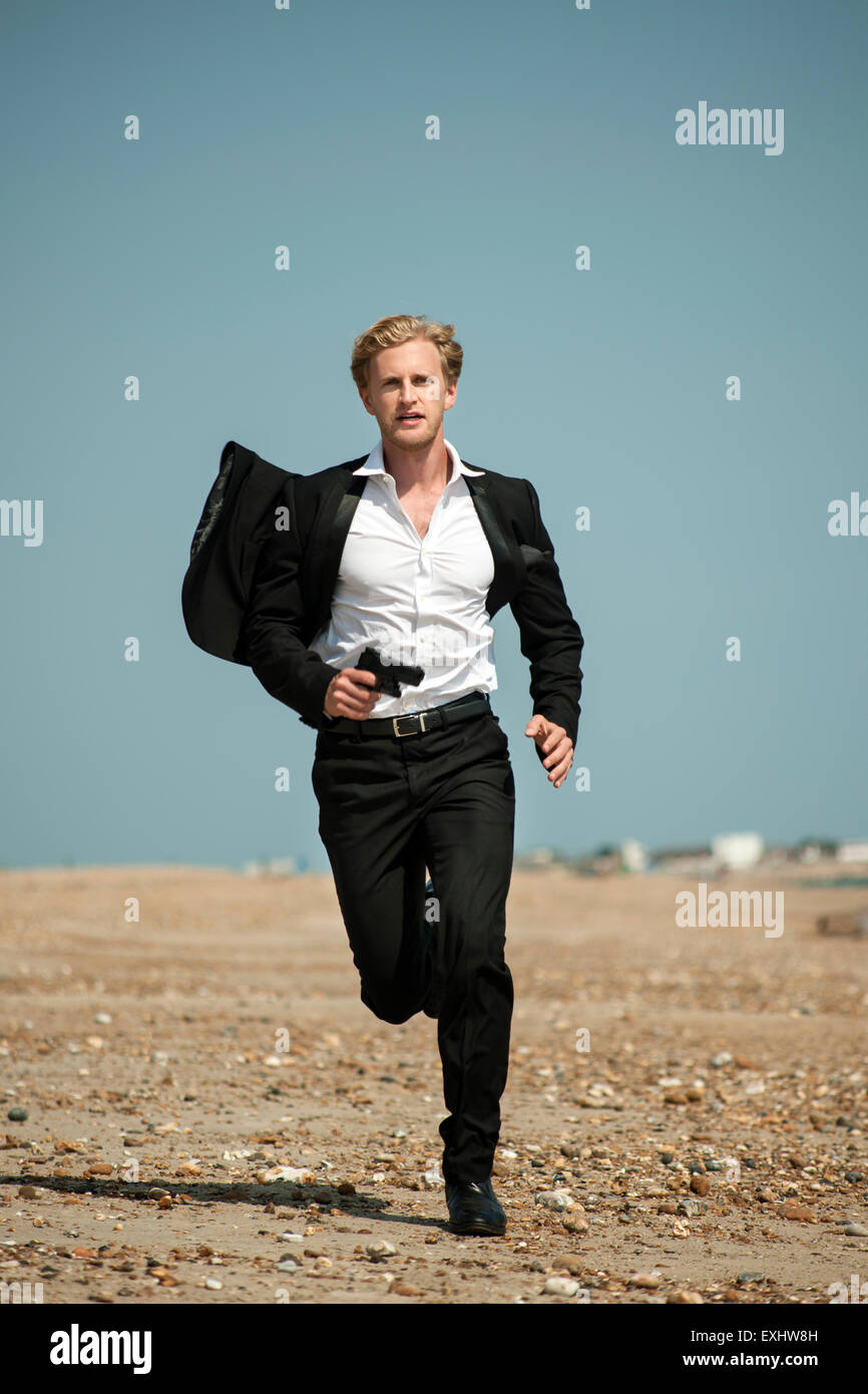 man in a black suit running after someone on the beach holding a gun. Stock Photo