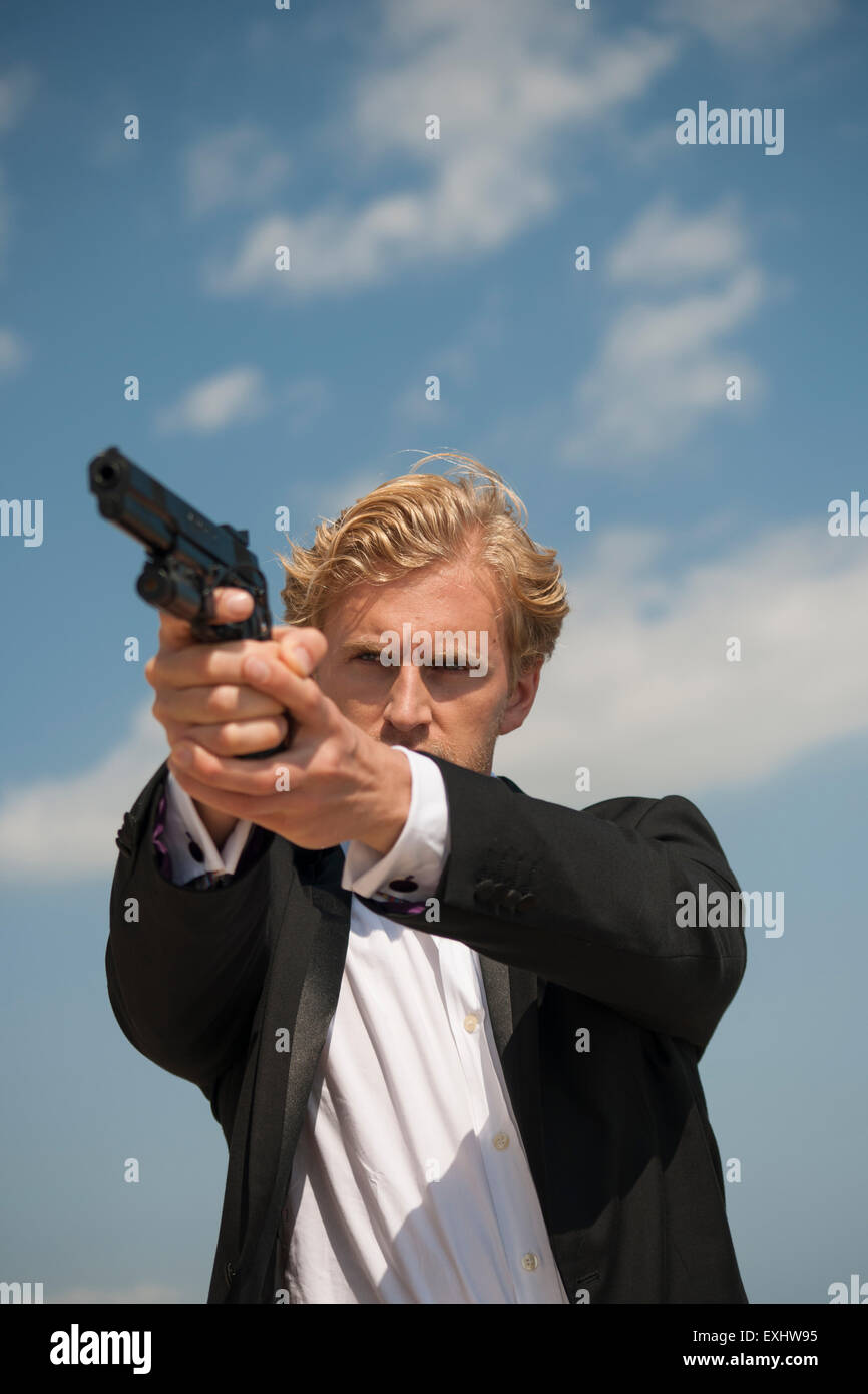 Man aiming a handgun, holding the gun with both hands wearing a black suit. - Stock Image