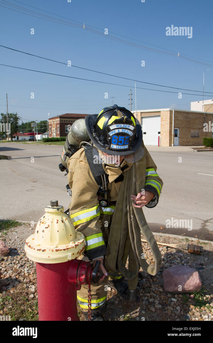 Female firefighter in rural volunteer fire department working with equipment. - Stock Image