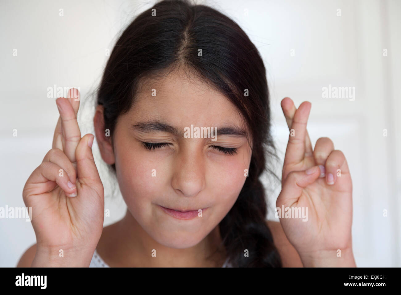 Teenage girl crossing her fingers with eyes closed - Stock Image