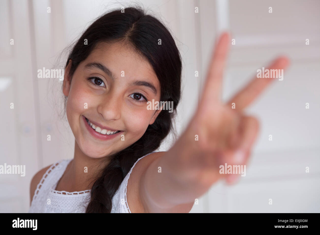 Happy teenage girl with V sign gesture - Stock Image