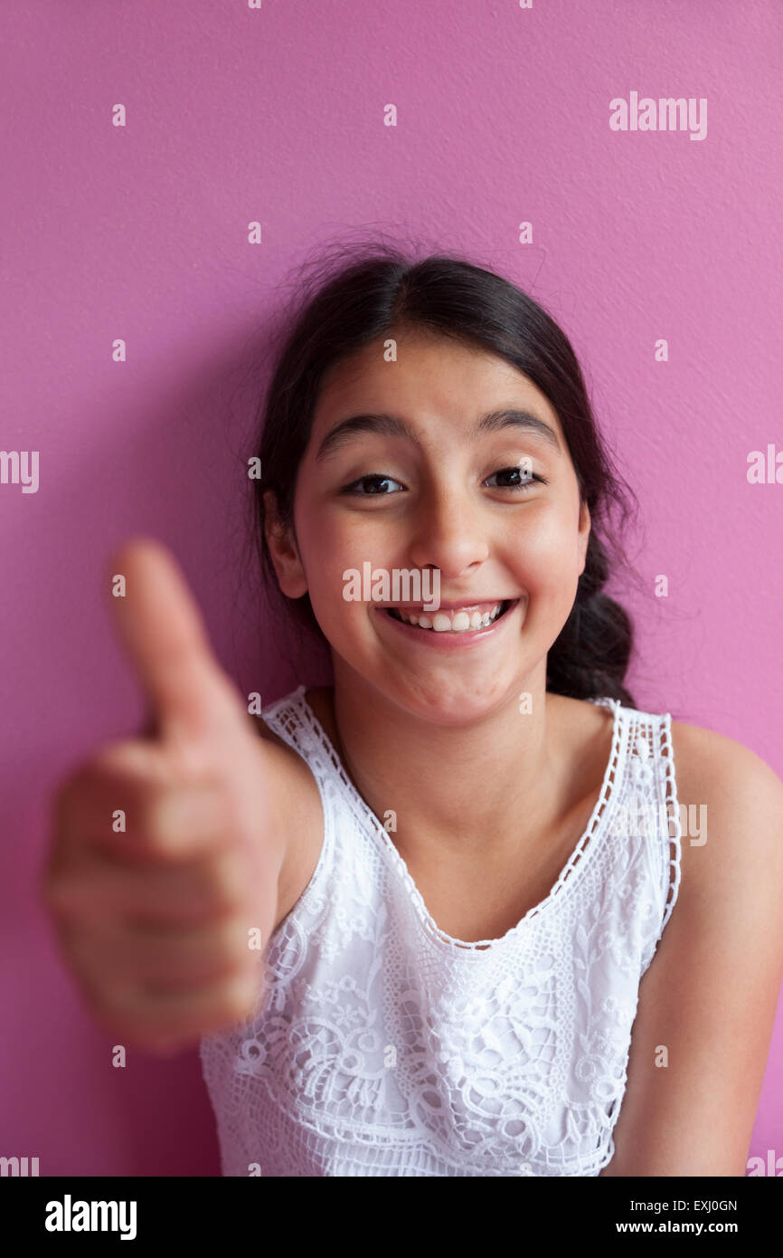 Happy teenage girl with thumb up gesture - Stock Image
