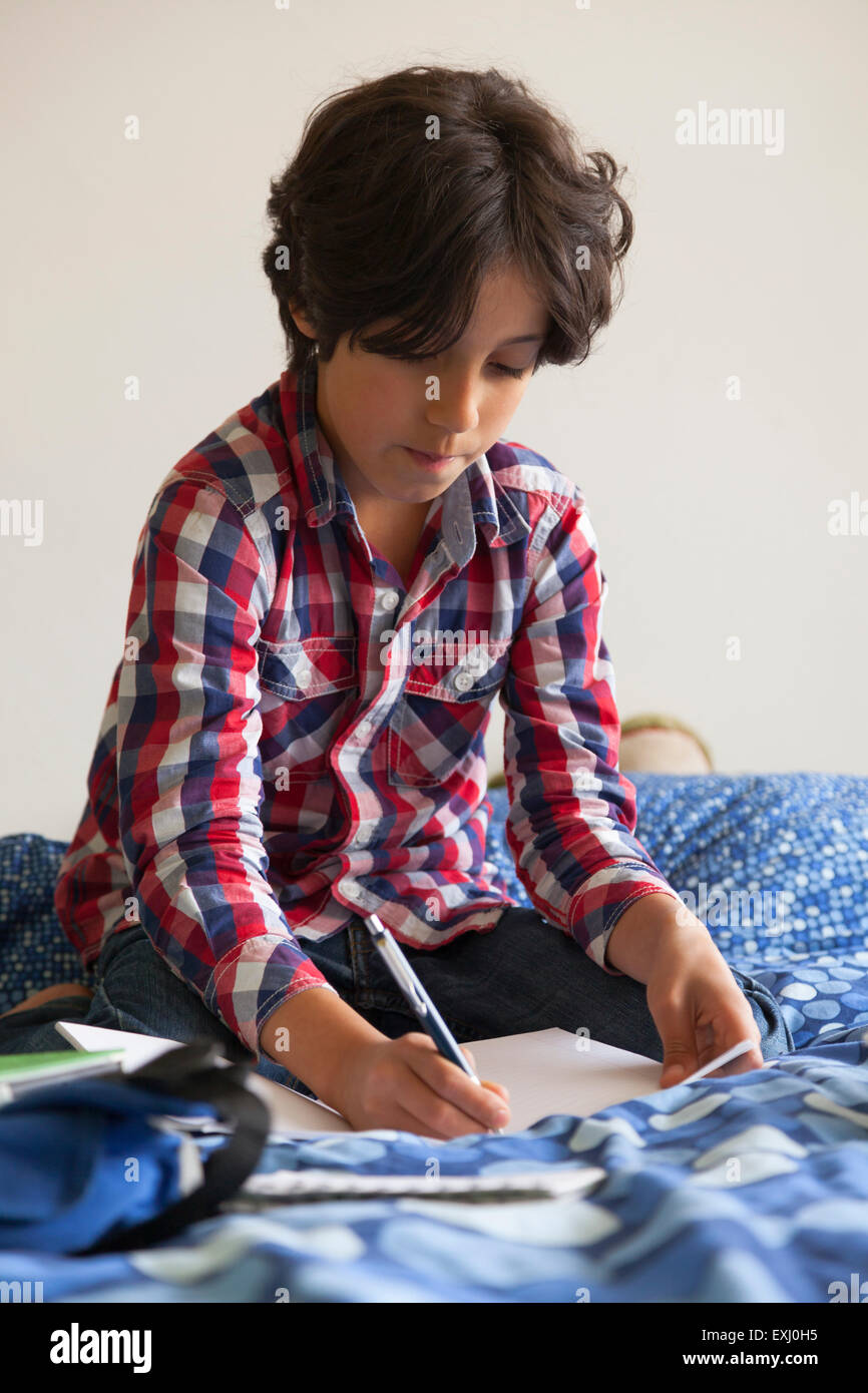 Ten year old boy making his homework sitting on his bed - Stock Image