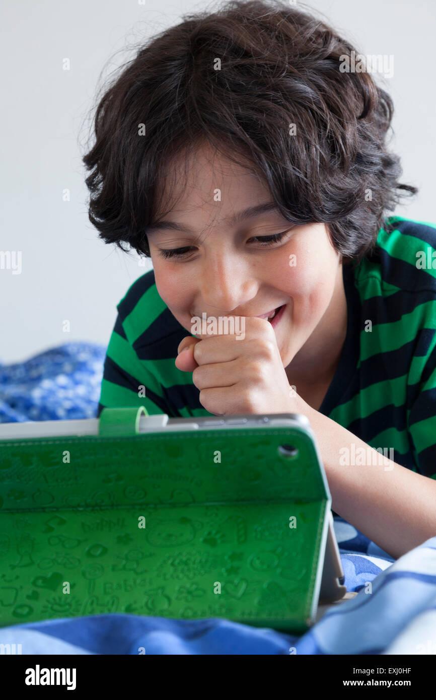 Teenage boy looking surprised at his digital tablet - Stock Image