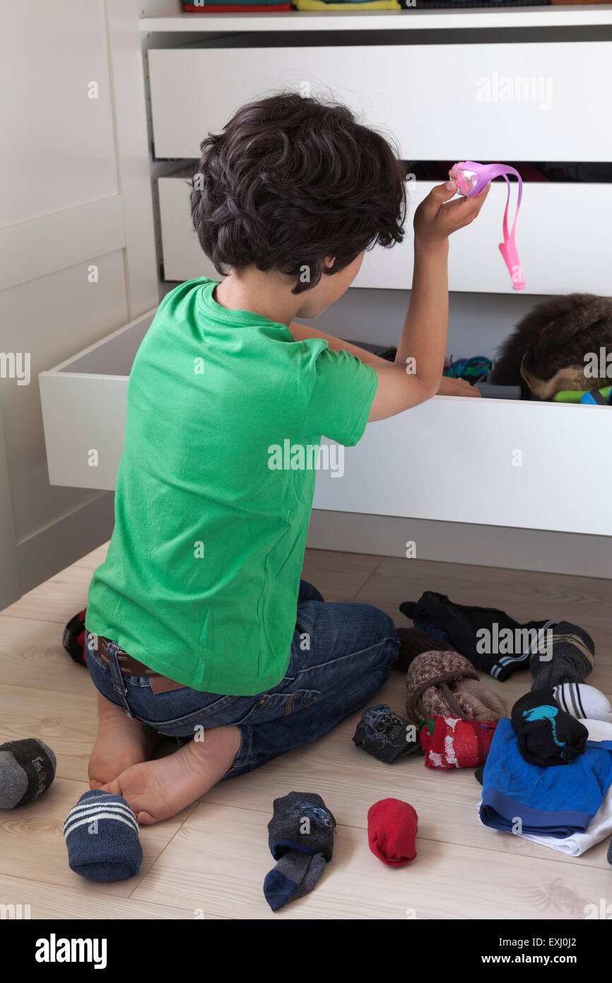 Teenage boy making a mess while searching into his wardrobe drawer - Stock Image