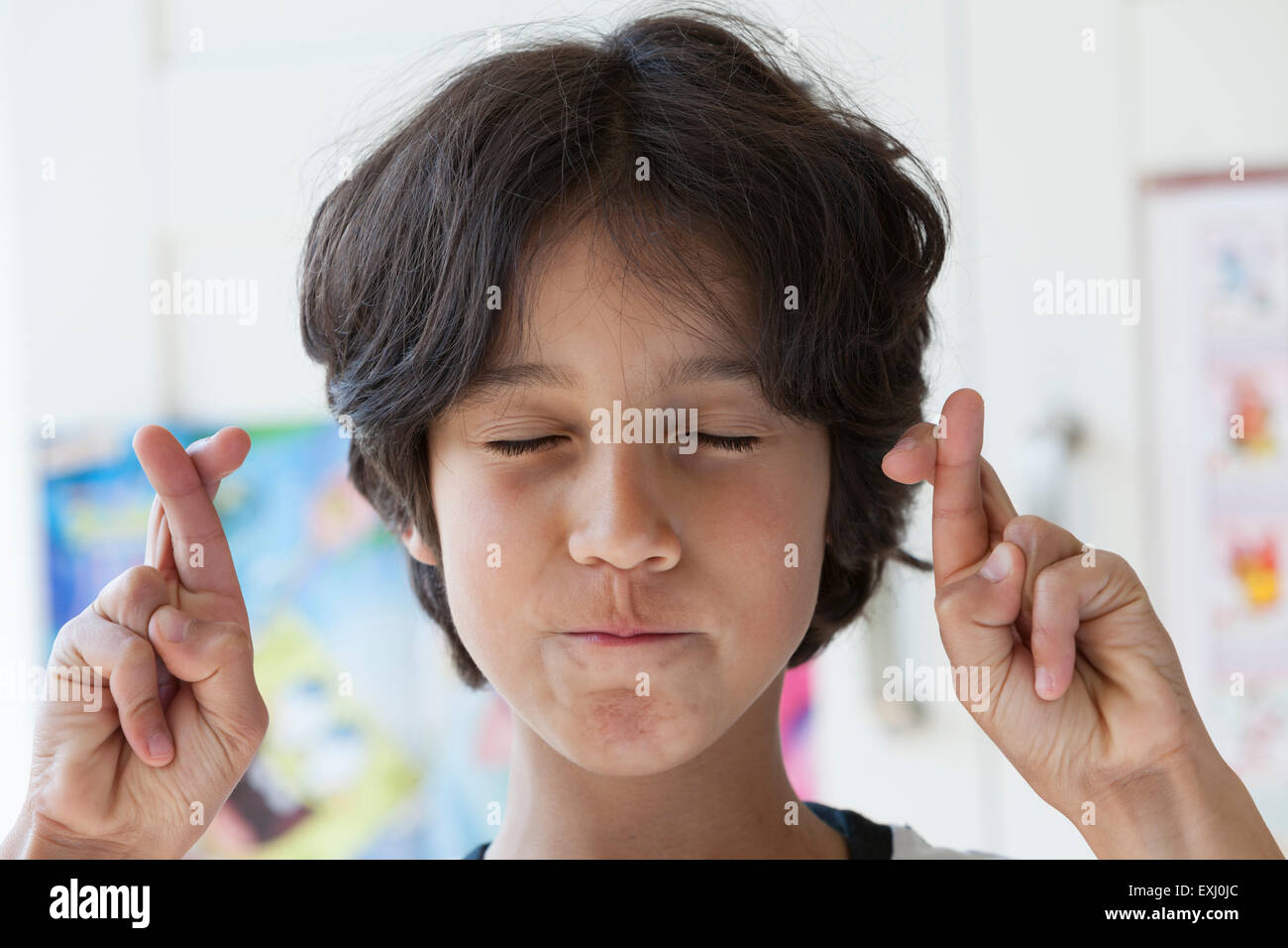 Teenage boy crossing his fingers with eyes closed - Stock Image