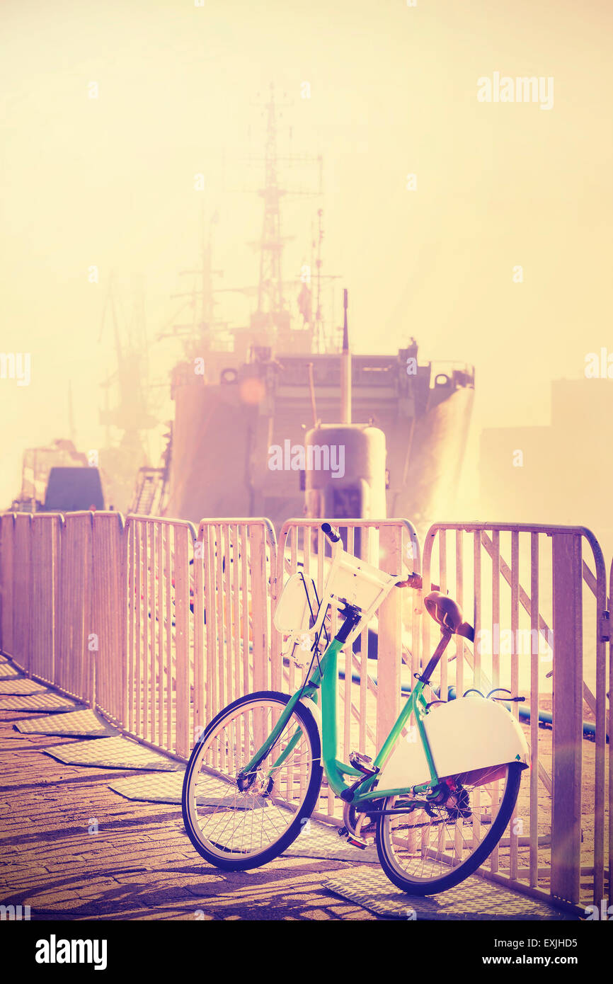Vintage toned bicycle parked by pier with ship in a distance, sunset lens flare effect. - Stock Image