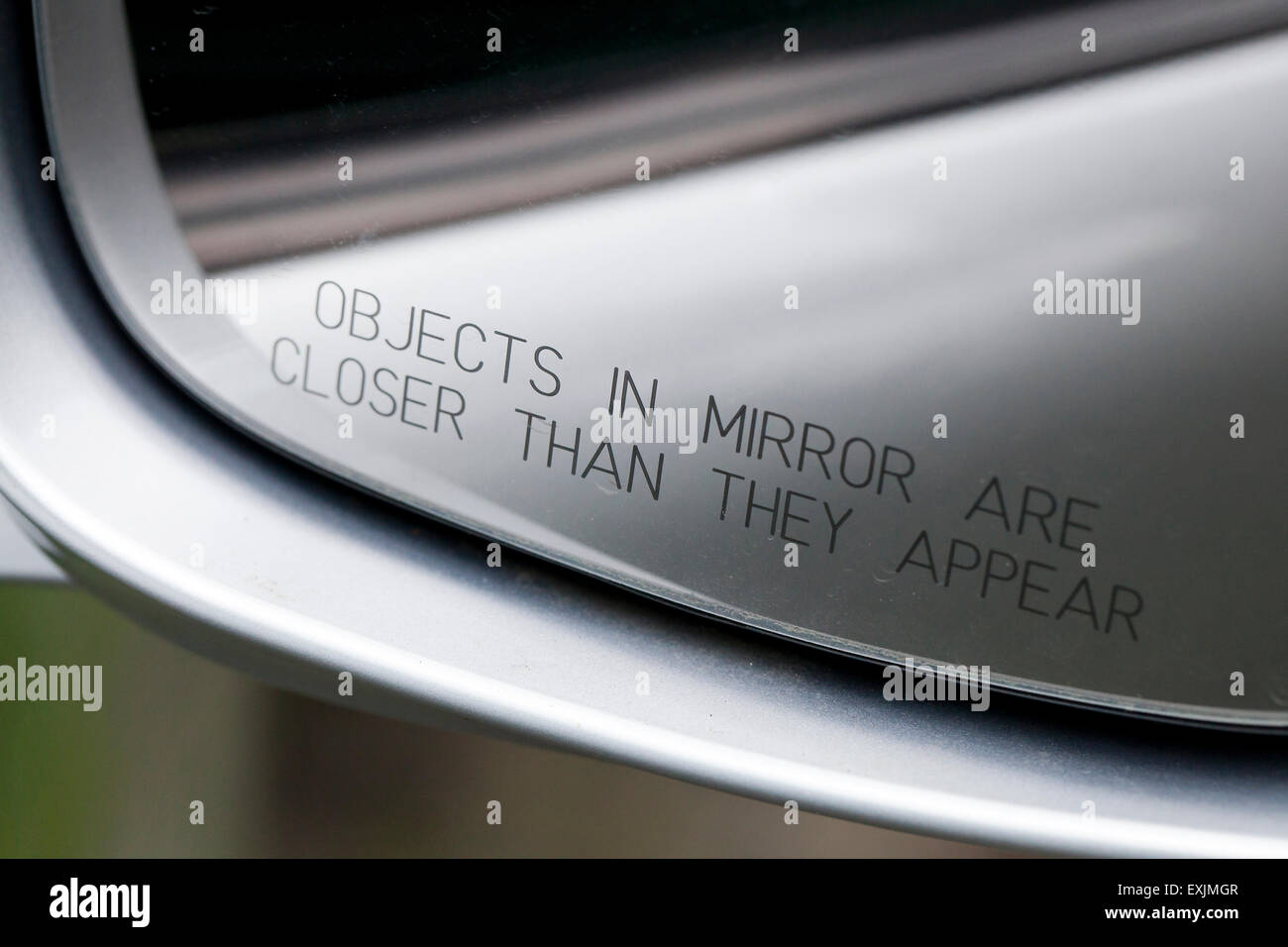 Objects in mirror are closer than they appear message in passenger side mirror of car - USA - Stock Image