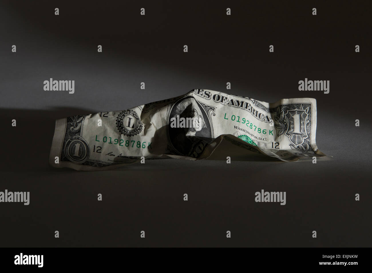 Crumpled American dollar bill on a black background - Stock Image