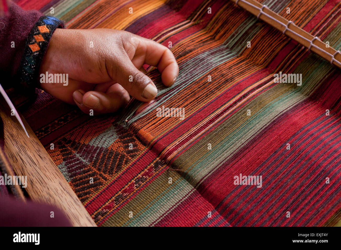 Peruvian man from Chinchero weaving traditional fabric using back strap loom - Stock Image