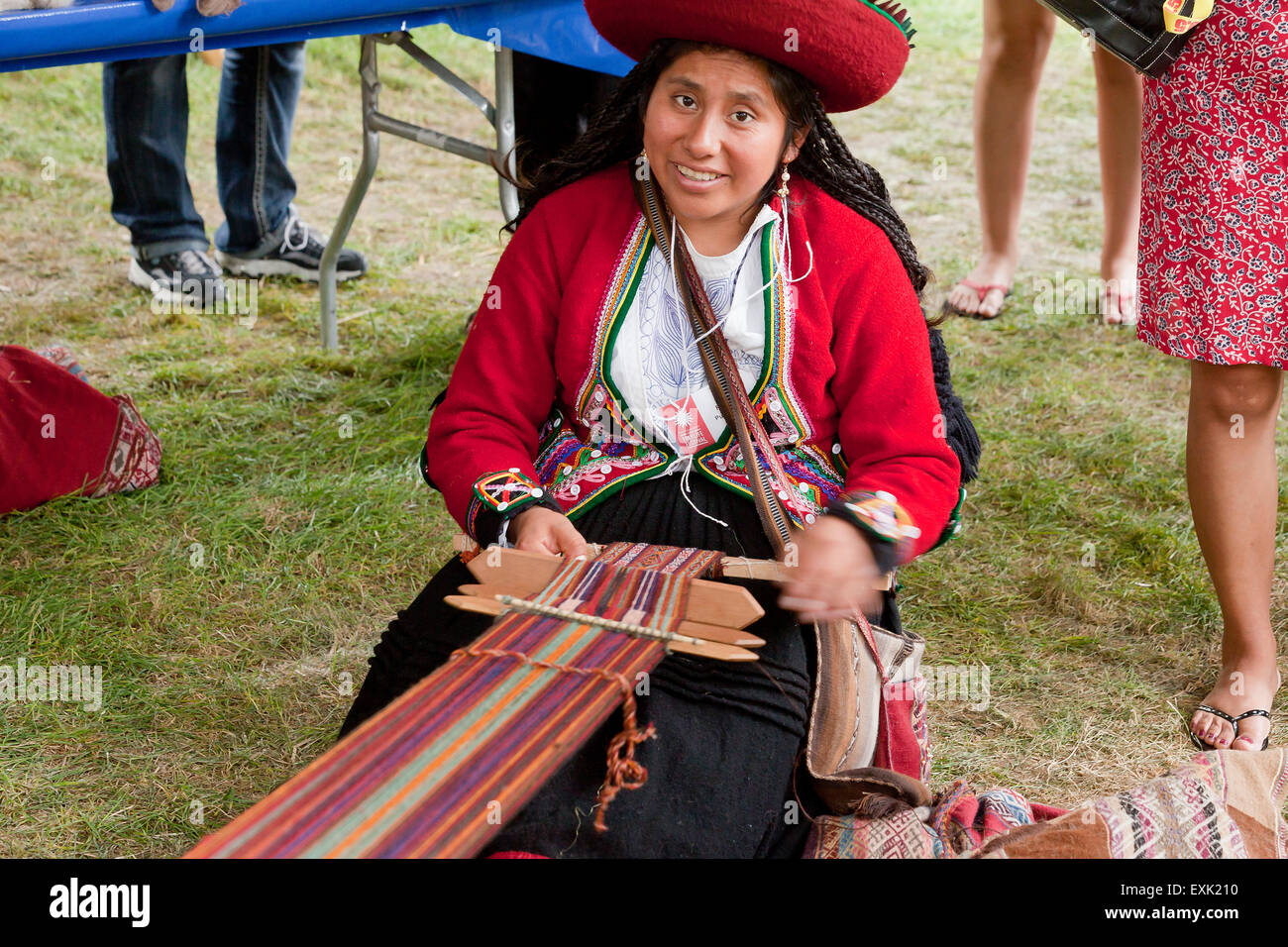 Peruvian woman from Chinchero weaving traditional fabric using a back strap loom - Stock Image