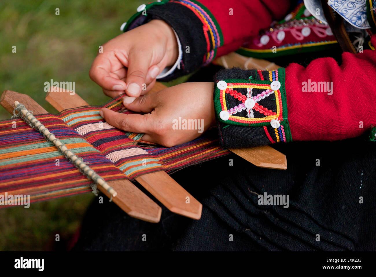 Peruvian woman from Chinchero weaving traditional fabric using back strap loom Stock Photo