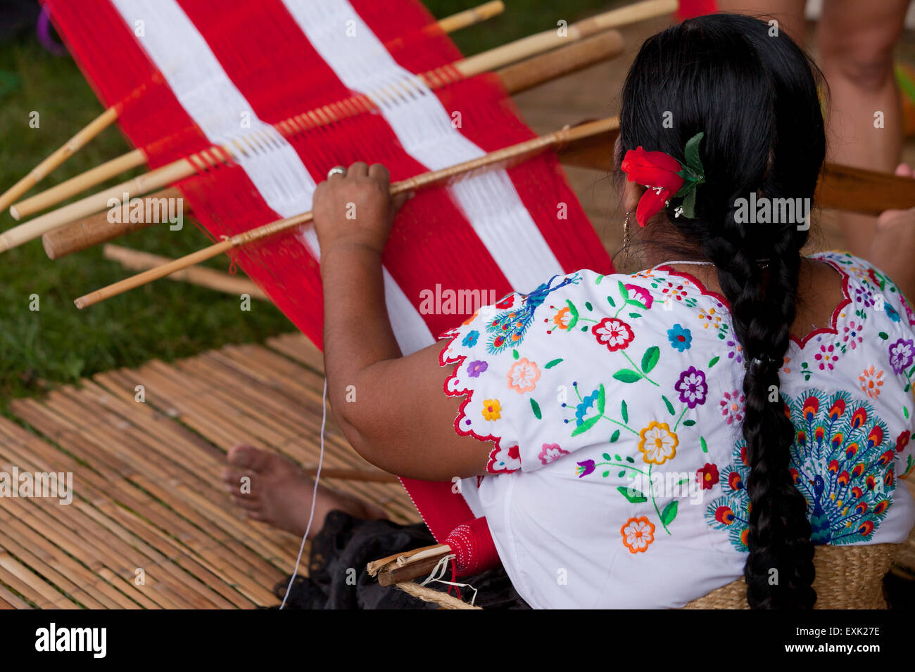 Peruvian woman from Chinchero weaving traditional fabric using back strap loom - Stock Image