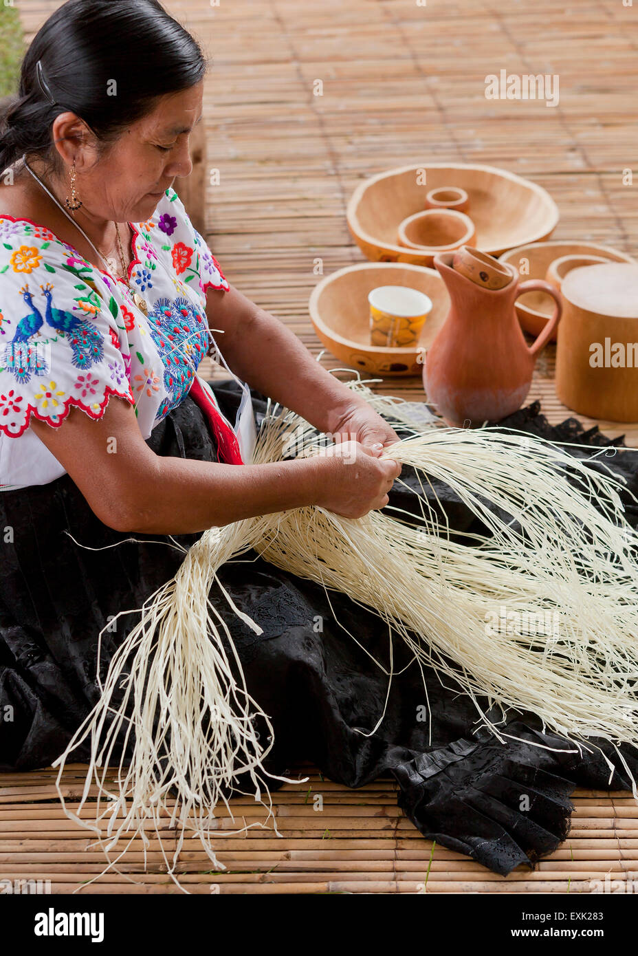 Indigenous Peruvian woman weaving a hat with natural fibers by hand - Stock Image