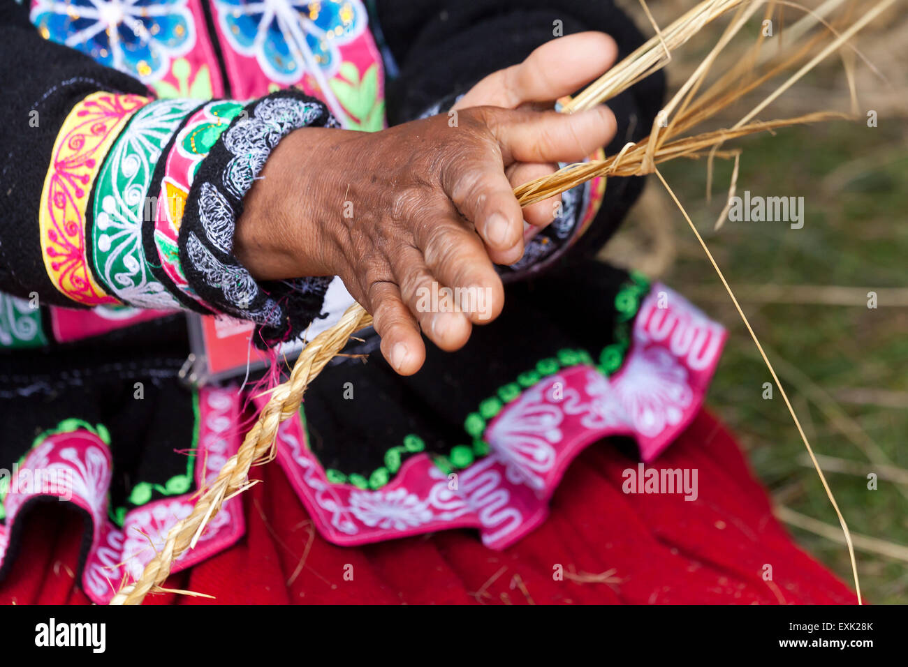 Indigenous Peruvian woman making rope from straw - Stock Image