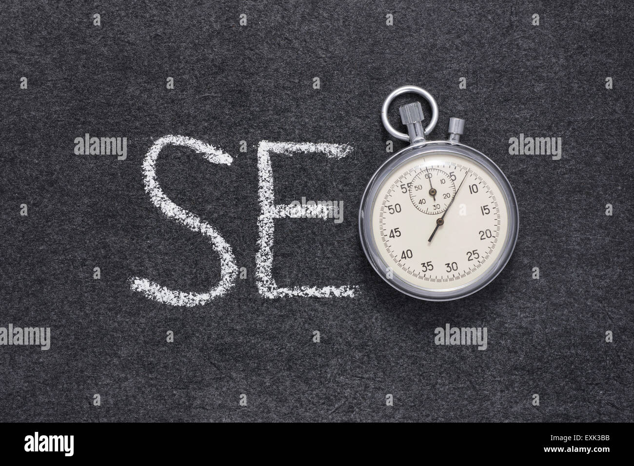 SEO abbreviation concept handwritten on chalkboard with vintage precise stopwatch used instead of O - Stock Image