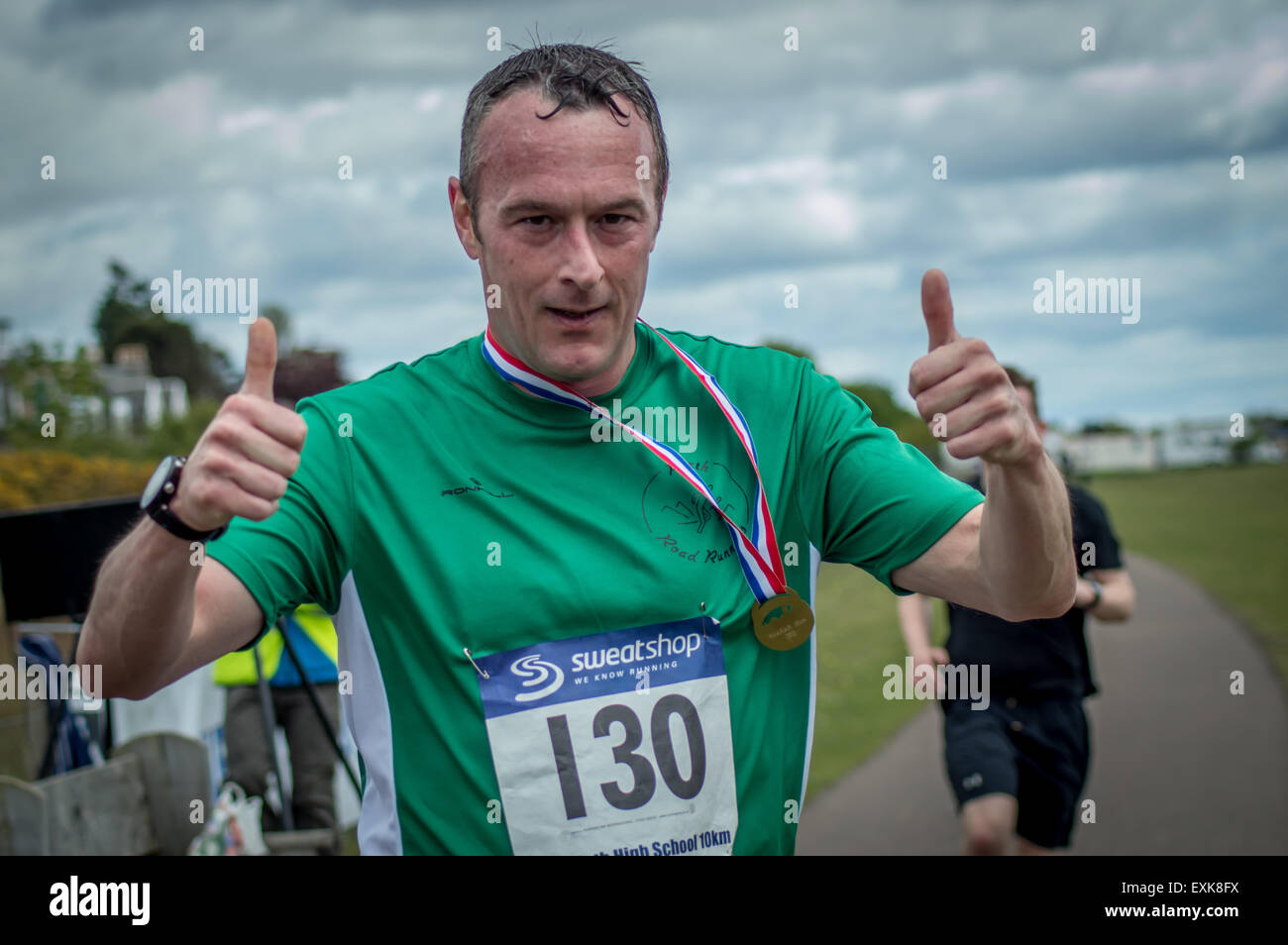 Male runner thumbs up on the finish line - Stock Image