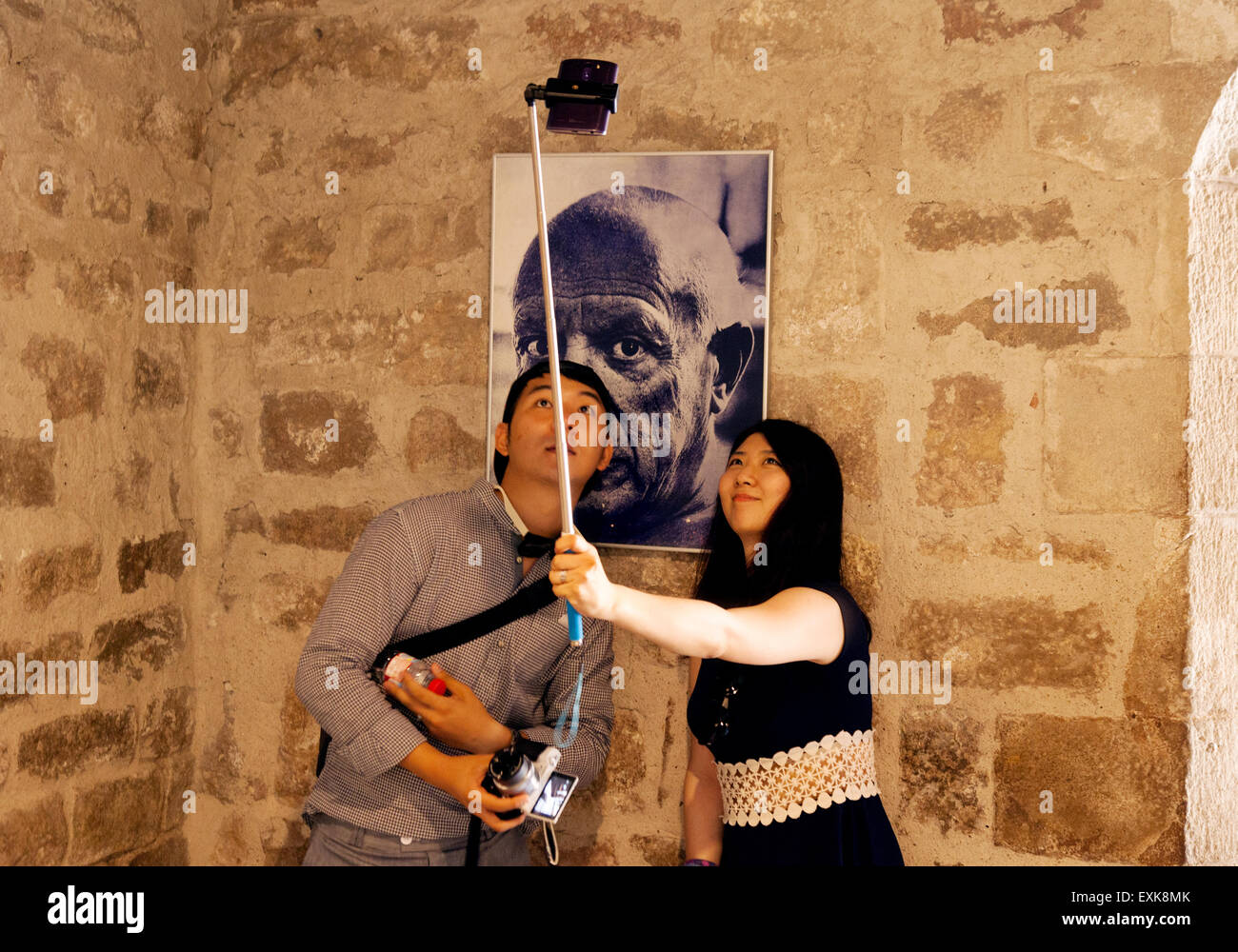 Asian tourists taking a selfie with a selfie stick with a photograph of Picasso,  Museu Picasso Museum, Barcelona - Stock Image