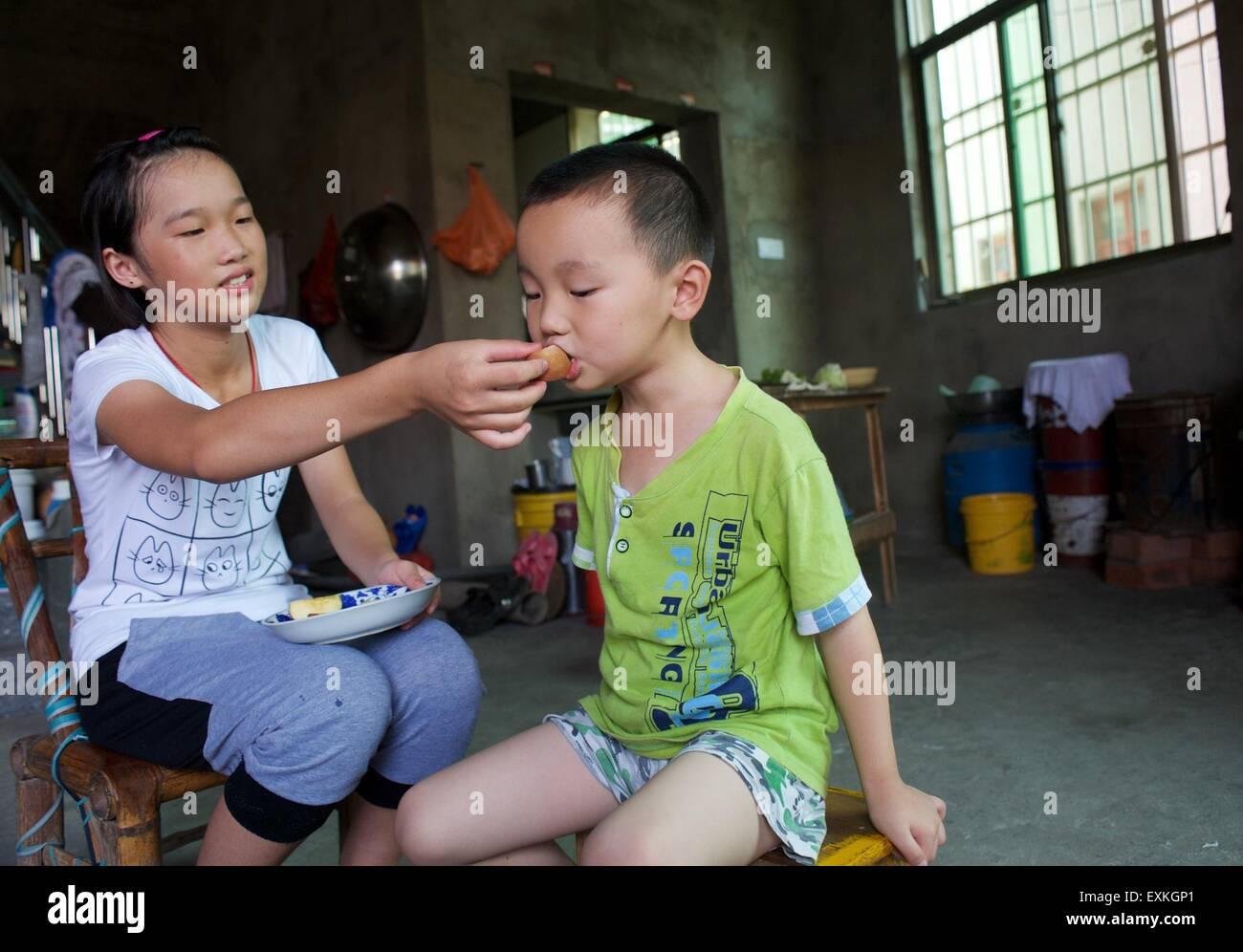 Nanchang, Nanchang City of east China's Jiangxi Province. 14th July, 2015. Li Wenyu (L) feeds her brother with - Stock Image