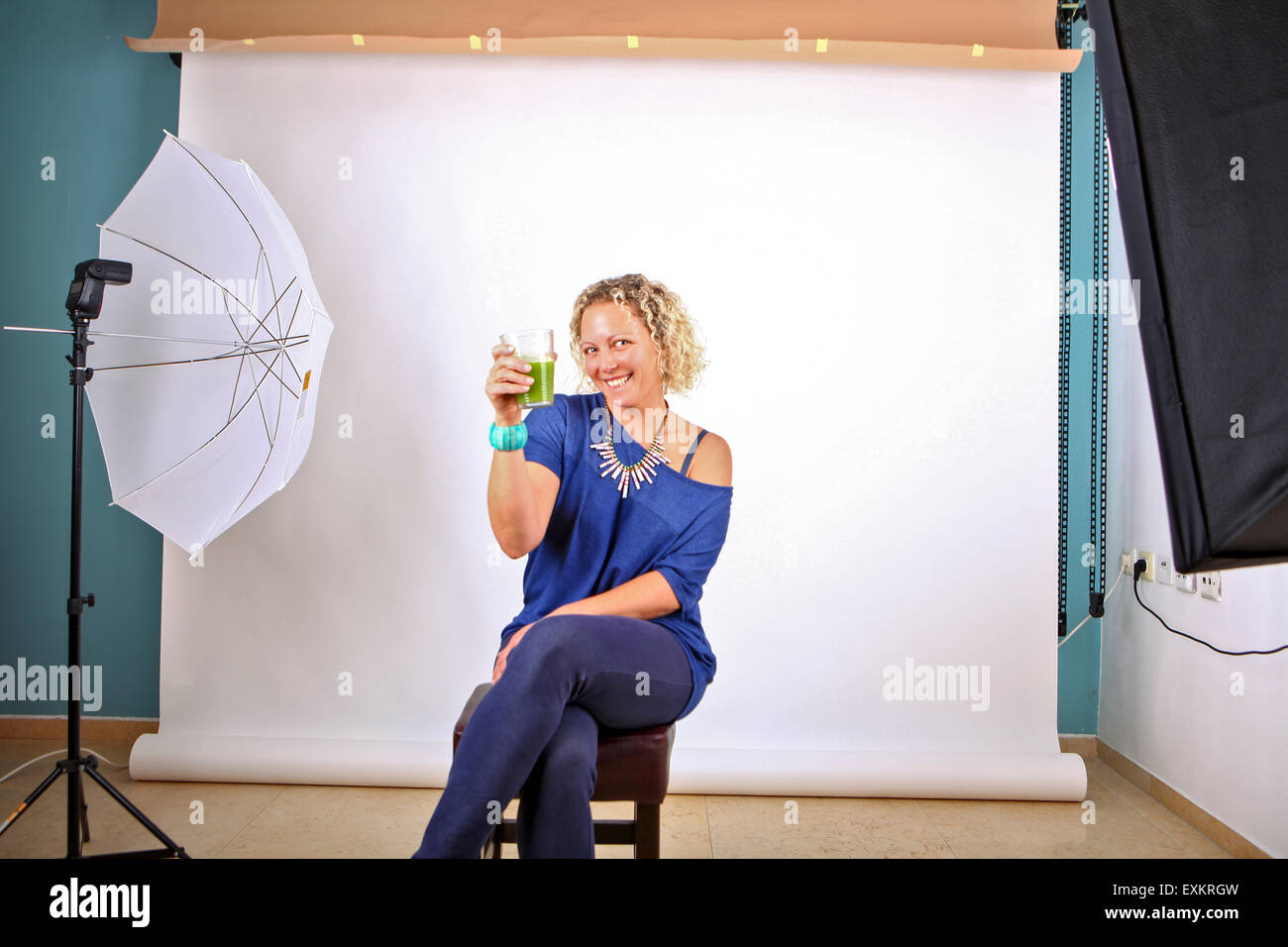 Model in photography studio drinking wheatgrass on the set - Stock Image
