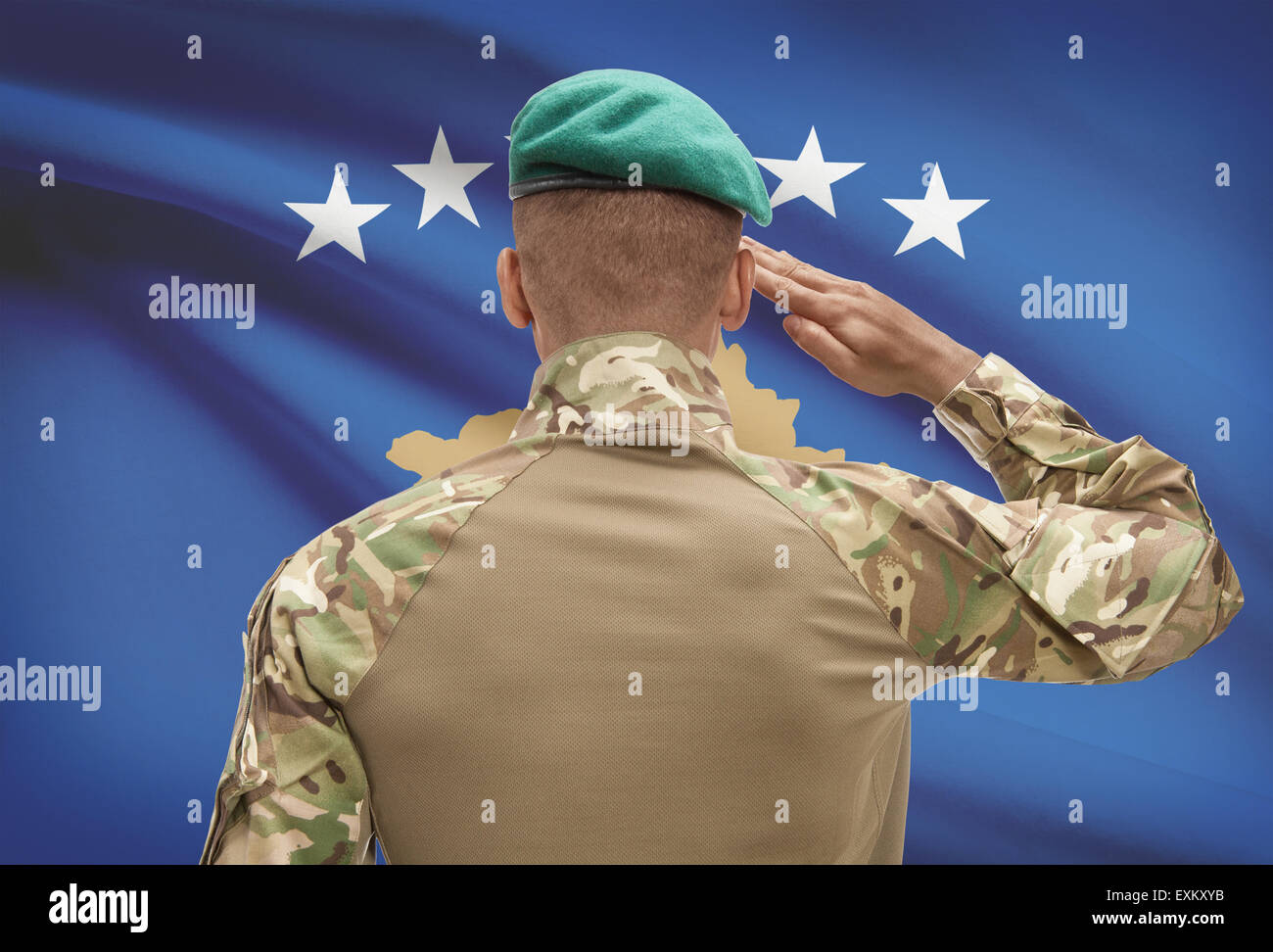 Dark-skinned soldier in hat facing national flag series - Kosovo Stock Photo