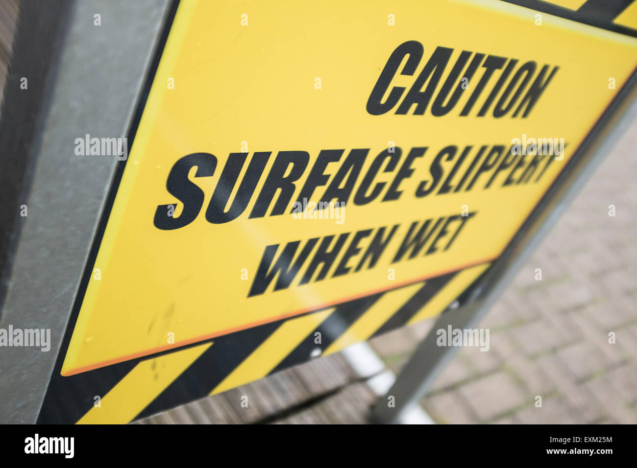 caution surface slippery when wet, yellow sign - Stock Image