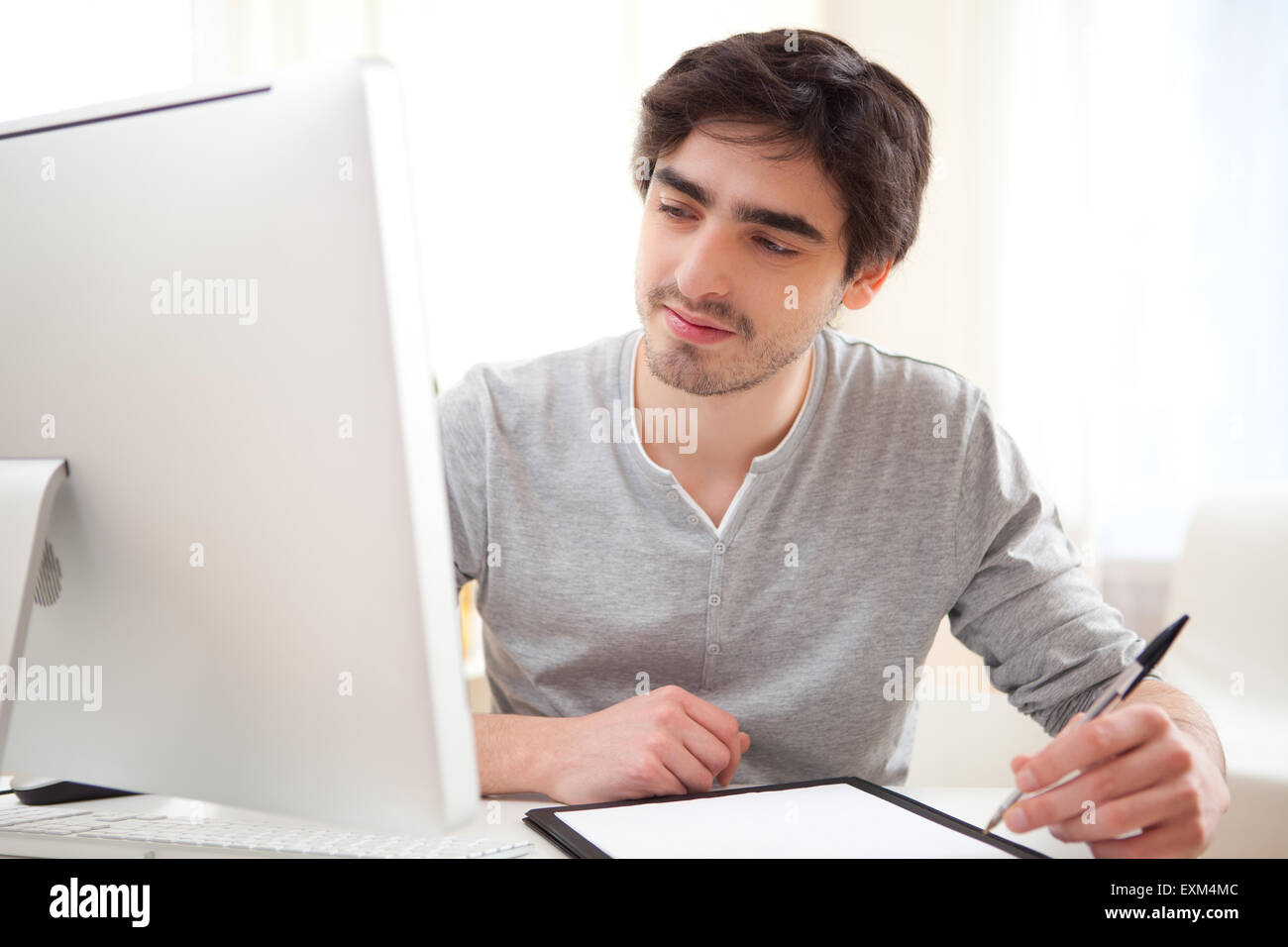 View of a young relaxed men writting at the office - Stock Image
