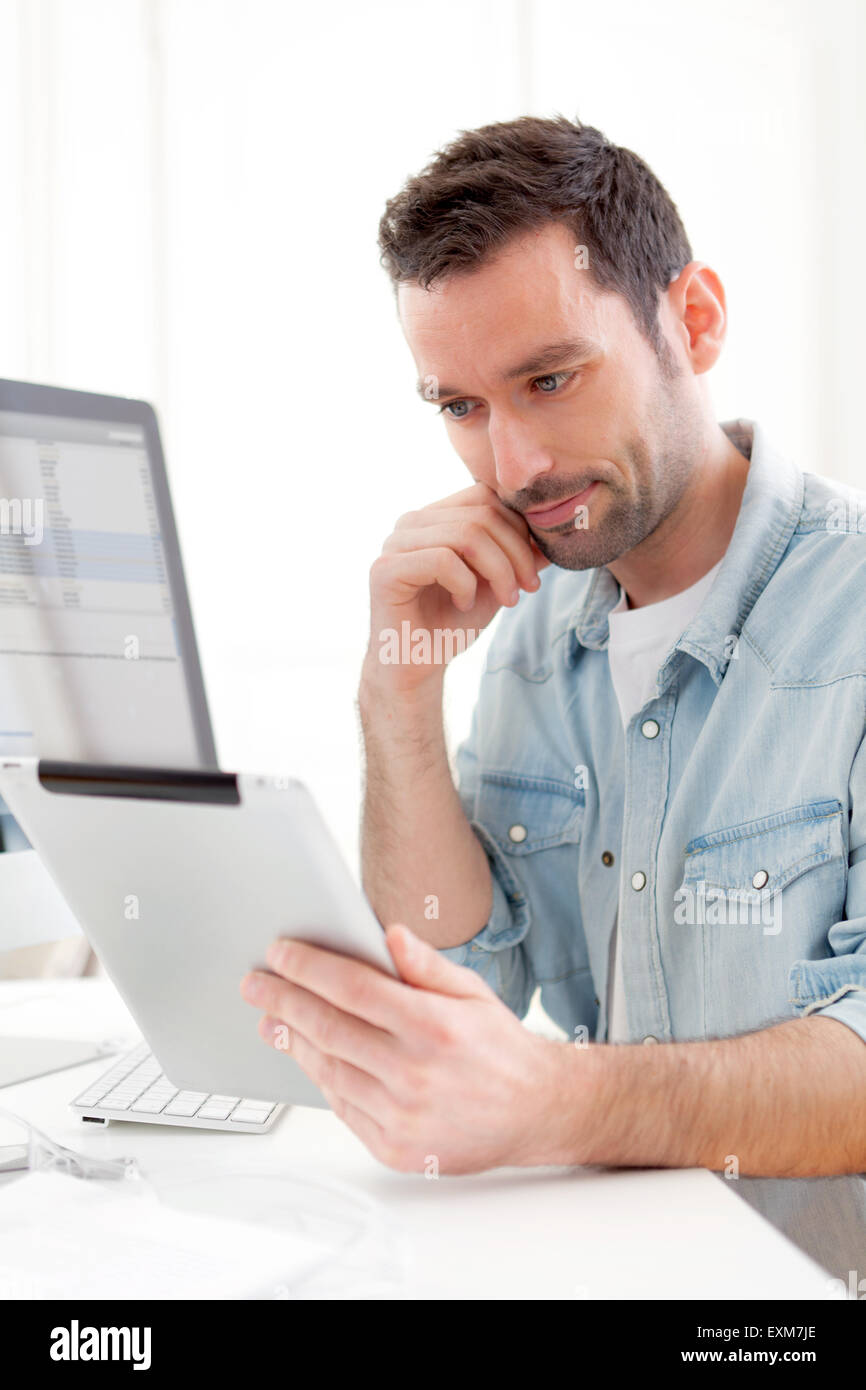 View of a Young relaxed man using tablet at home - Stock Image