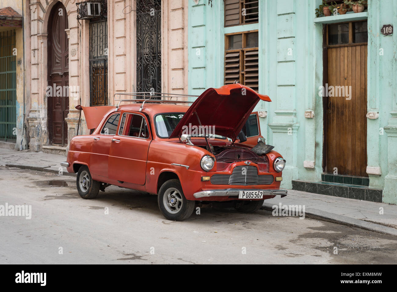 A red Cuban classic car parked undergoing repairs in a central Havana street - Stock Image
