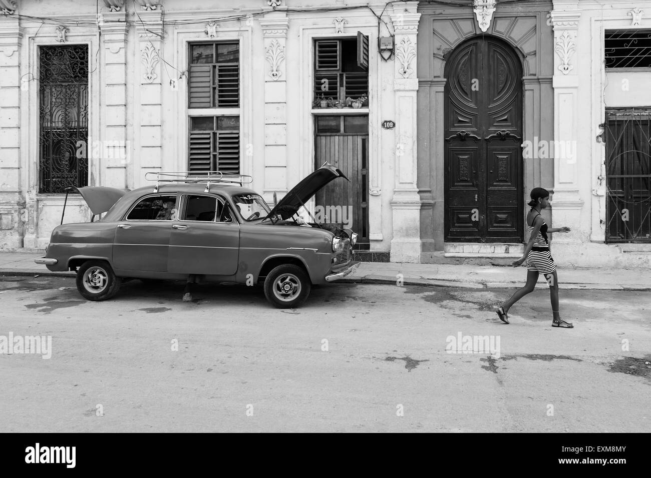 A Cuban classic car parked undergoing repairs in a central Havana street with a Cuban girl walking by. Cuba. - Stock Image