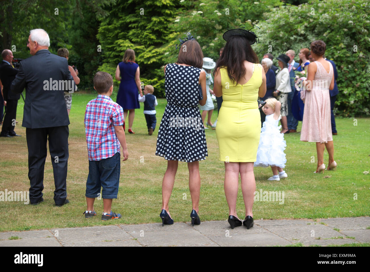 Guests at a summer wedding gather outside for group photos in Herefordshire UK - Stock Image