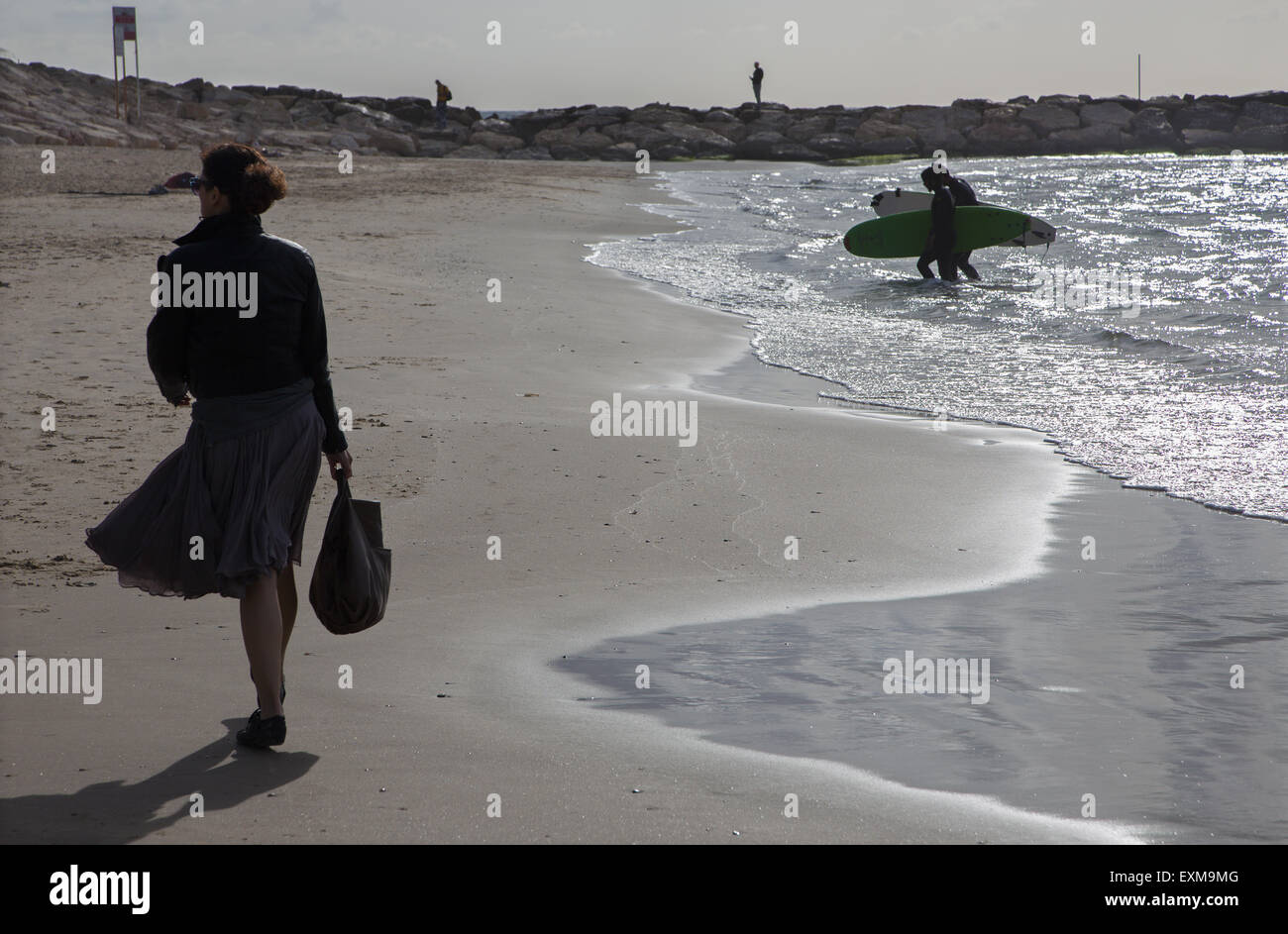 TEL AVIV, ISRAEL - MARCH 2, 2015: The silhouette of walked woman and surfers on the beach of Tel Aviv. - Stock Image