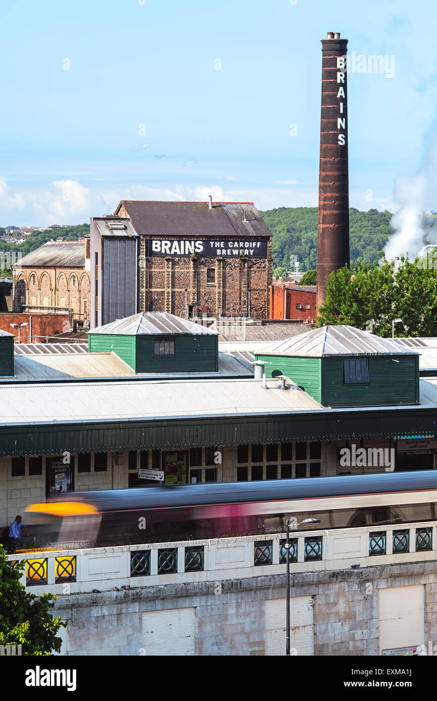 The old chimney of Brains Brewery and Cardiff train station in the foreground. - Stock Image