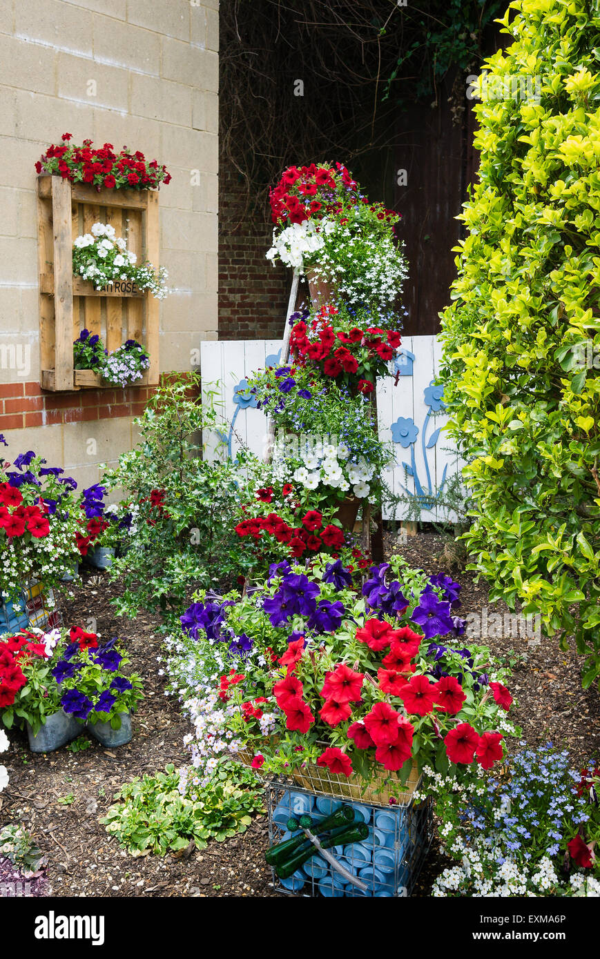 Small urban garden decorated by Waitrose using recycled material and bedding plantsMaking do - Stock Image