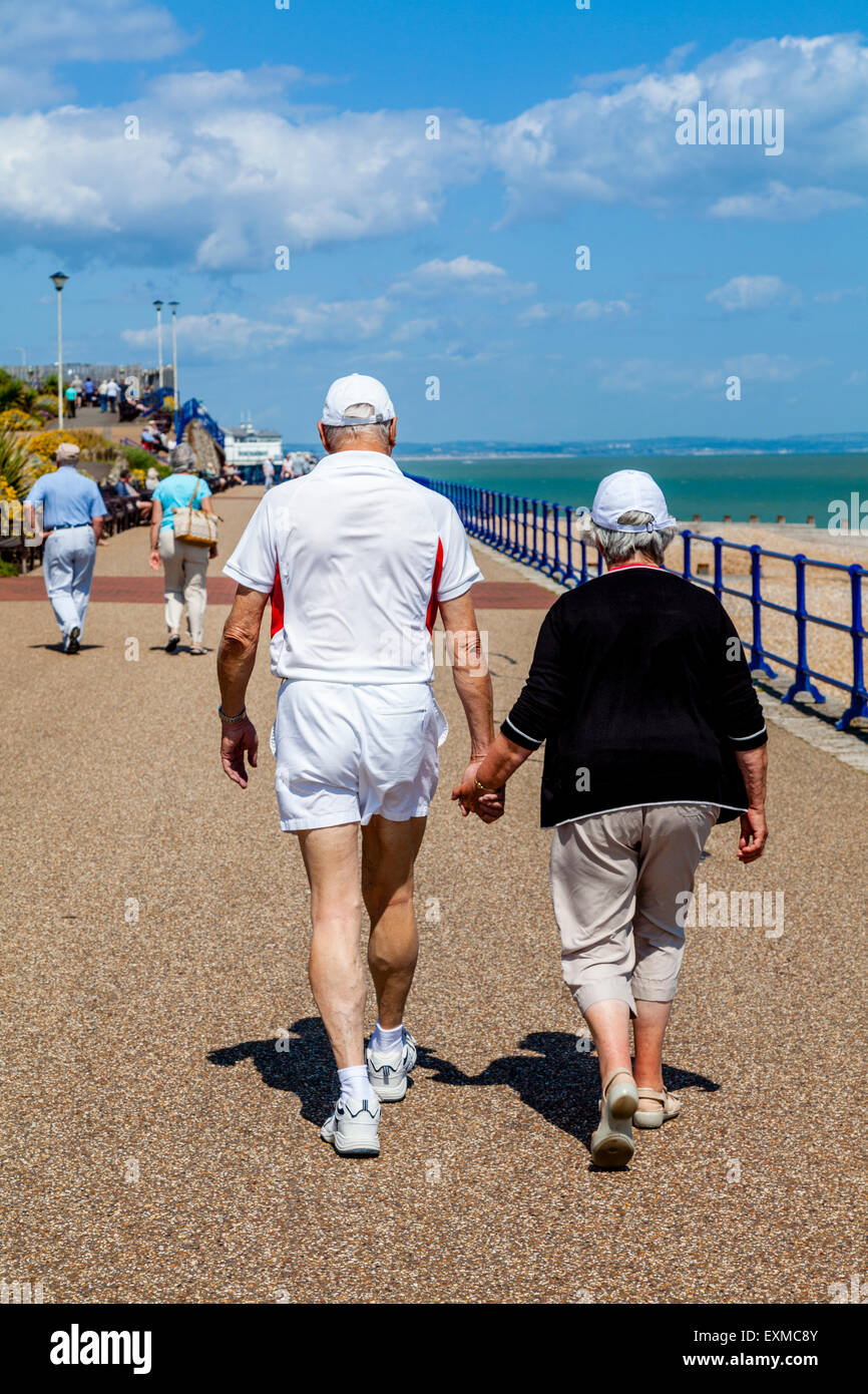 An Elderly Couple Walking Along The Seafront, Eastbourne, Sussex, UK - Stock Image