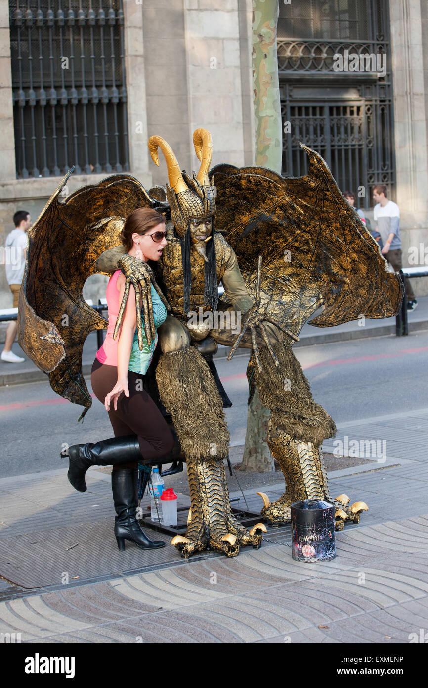 Live devil statue, street performer posing with girl on La Rambla in Barcelona, Catalonia, Spain. - Stock Image