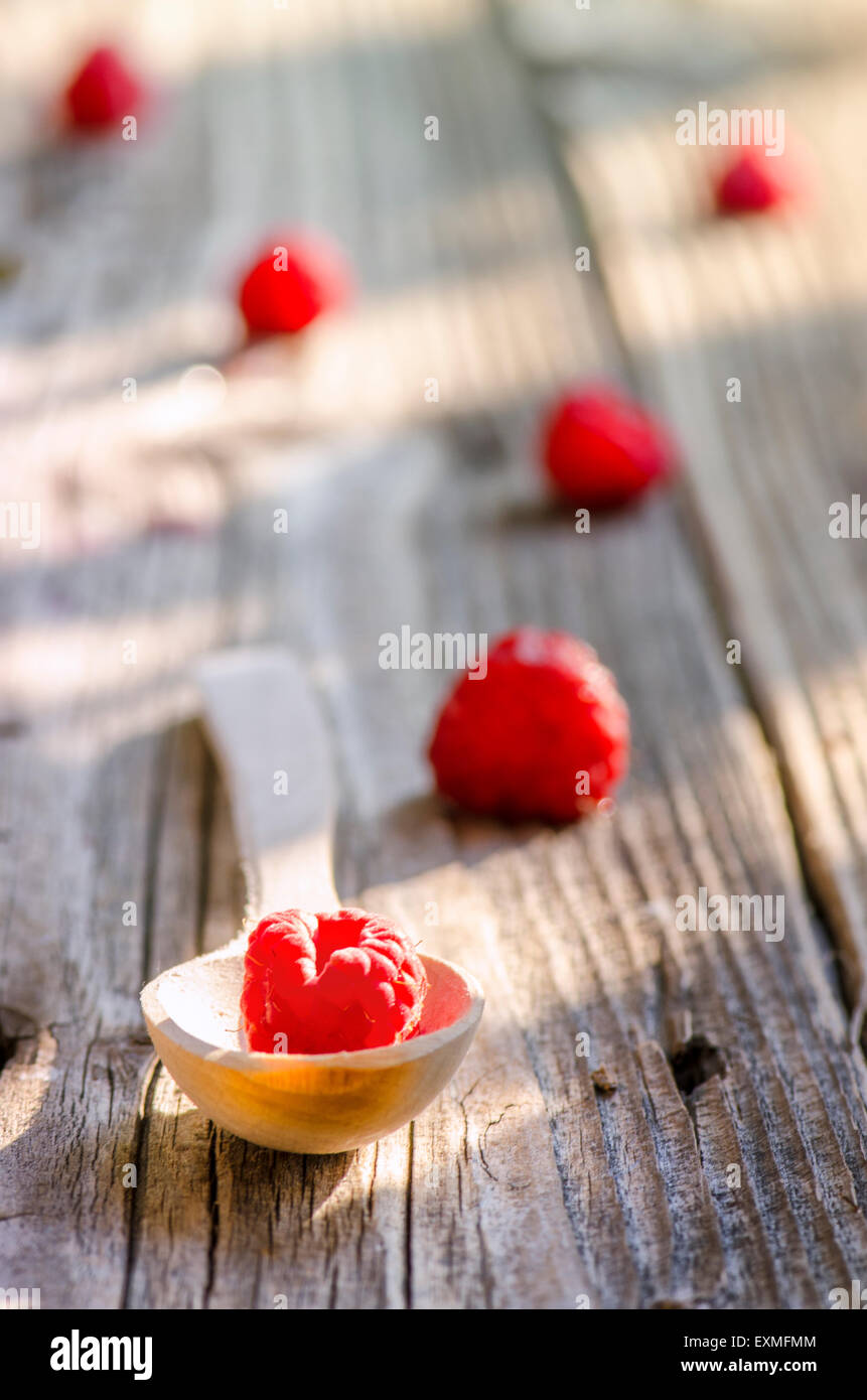 Rasberry in wooden spoon isolated on vintage wooden background - Stock Image