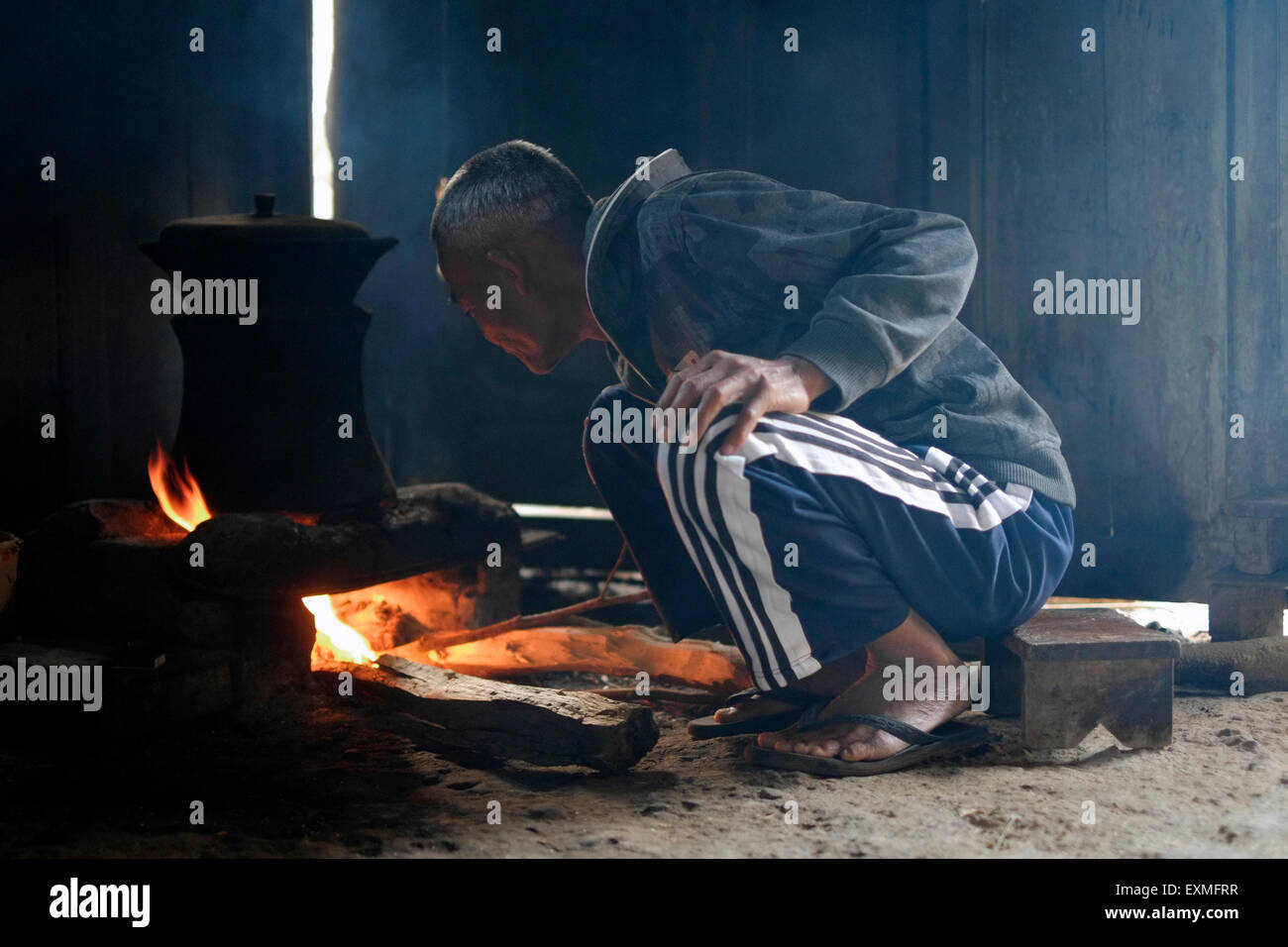 older man cooking with an old pot over a wood burning open fire in a rural house on mount lawu near solo java indonesia - Stock Image