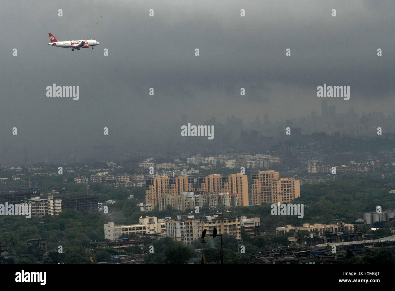 A Kingfisher Airlines commercial plane approaching the airport amidst dense monsoon clouds in Bombay Mumbai - Stock Image