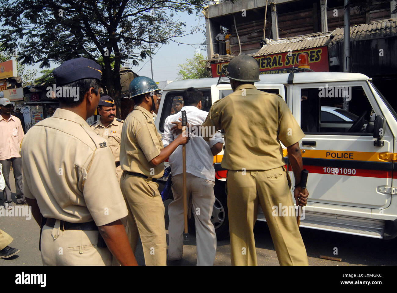 Police personnel charge lathi against a dalit rioter in Bhandup after the Dalit community resort to violent protests - Stock Image