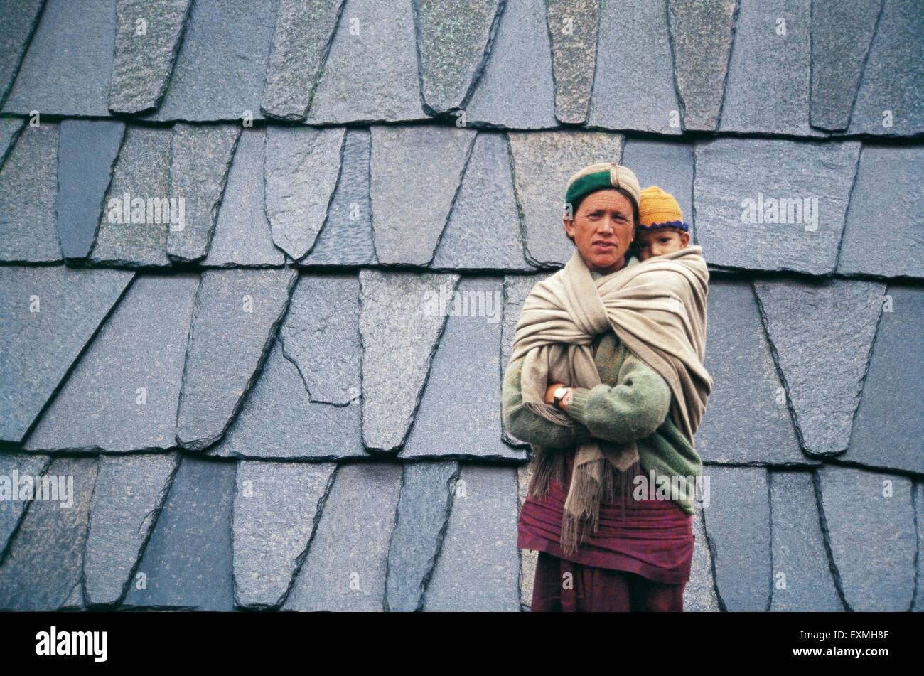 Rural lady tied child on back ; India - Stock Image