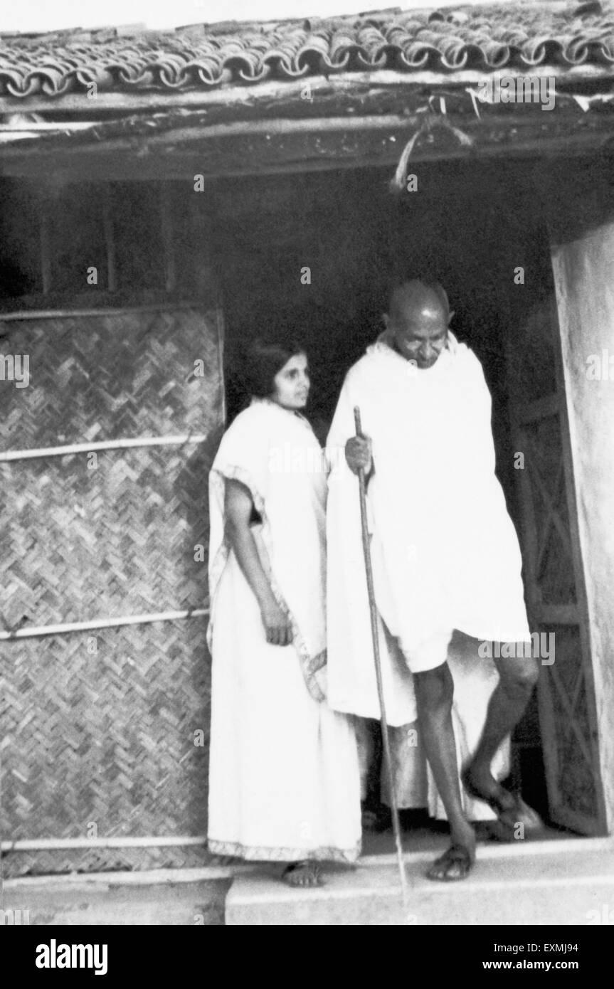 Mahatma Gandhi ; accompanied by coashramite Chandan Kalelkar ; leaving his hut at Sevagram Ashram ; 1940 NO MR - Stock Image