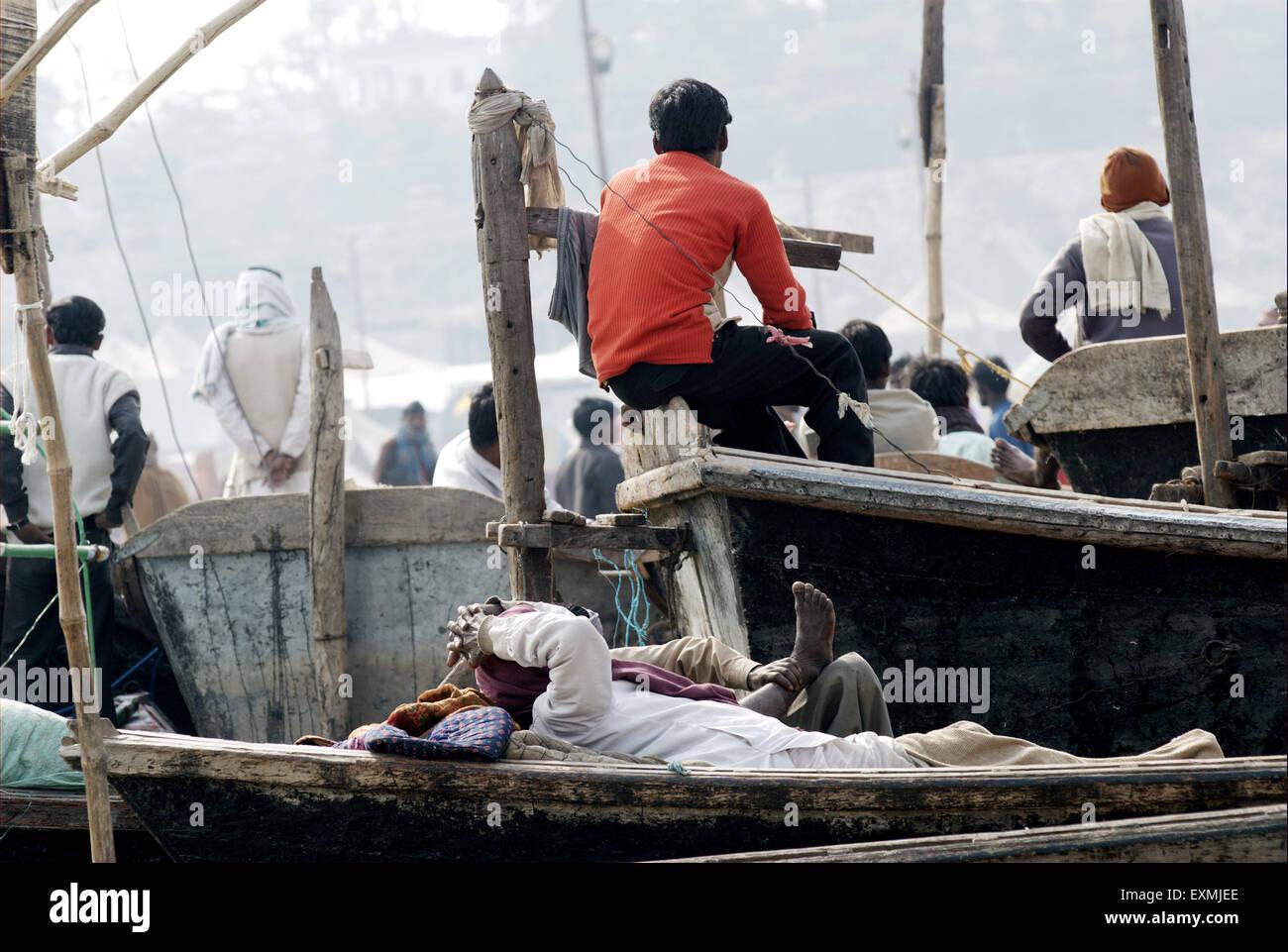 Devotee take nap on boat at confluence of Ganges; Yamuna and Saraswati rivers to take holy dip Ardh Kumbh Mela Allahabad - Stock Image