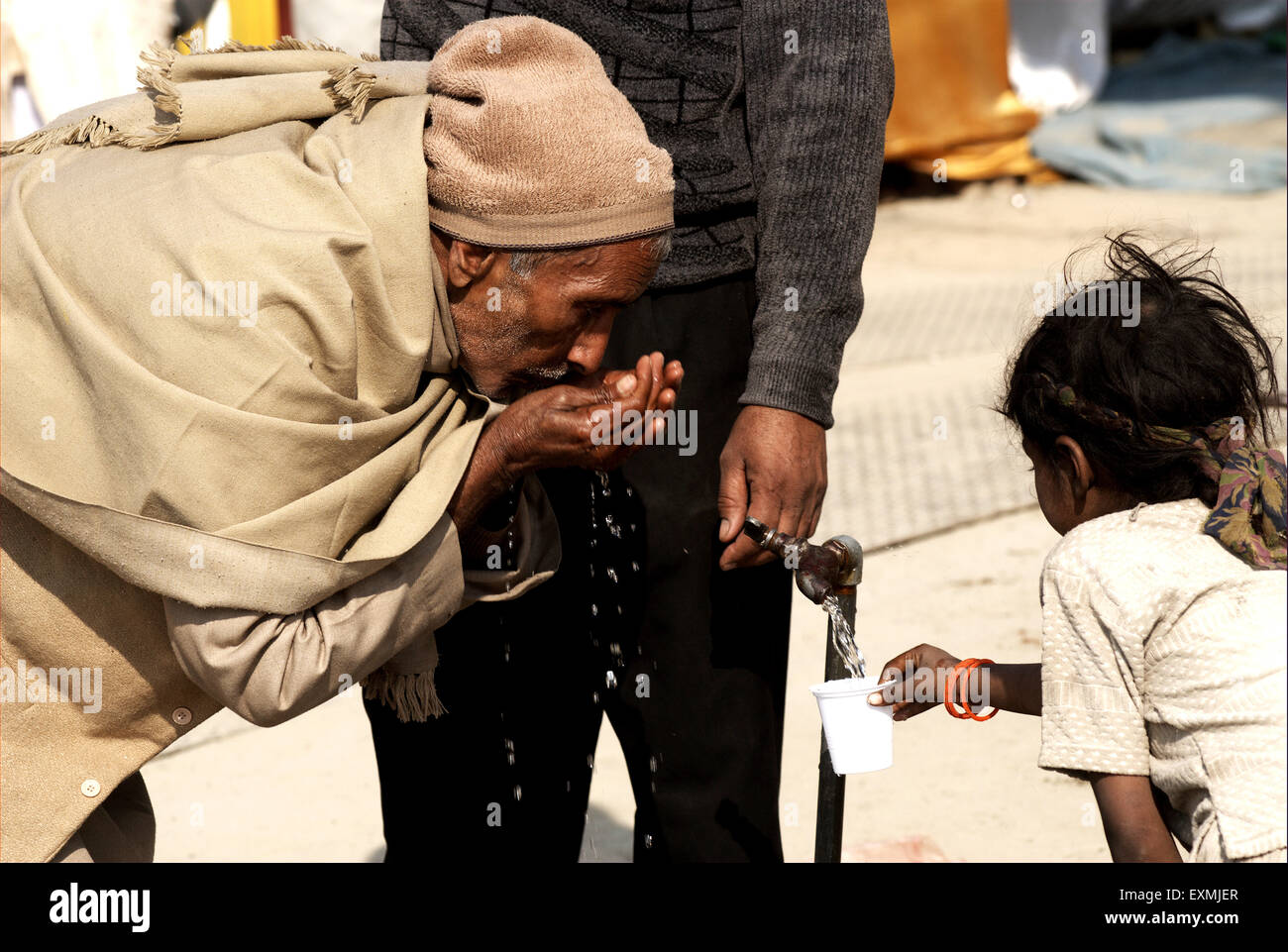 Old man and girl child quench thirst from tap at Allahabad; Uttar Pradesh; India - Stock Image