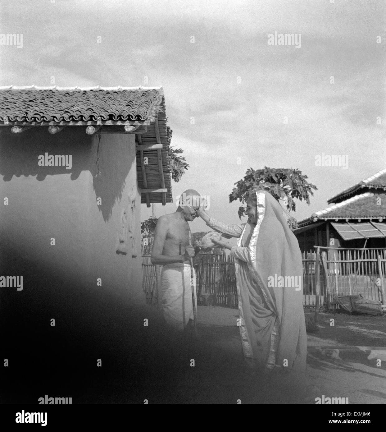 Mahatma Gandhi being greeted by a Parsi woman and presented a coconut in front of his hut at Sevagram Ashram ; Jan - Stock Image