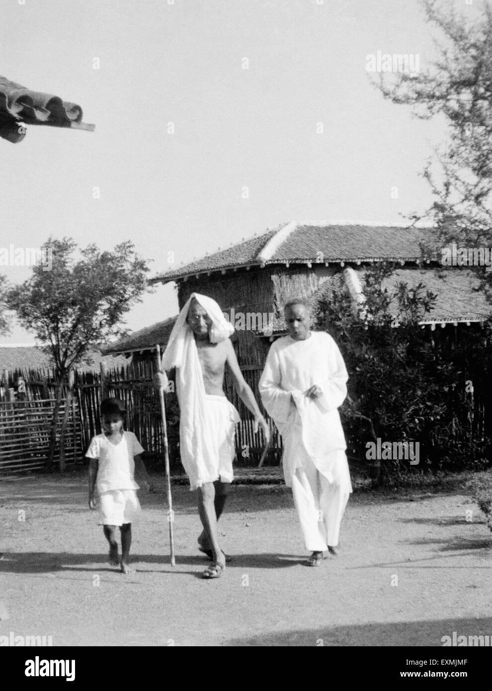 Mahatma Gandhi walking with Dr. Das and a boy at Sevagram Ashram ; 1940 NO MR - Stock Image