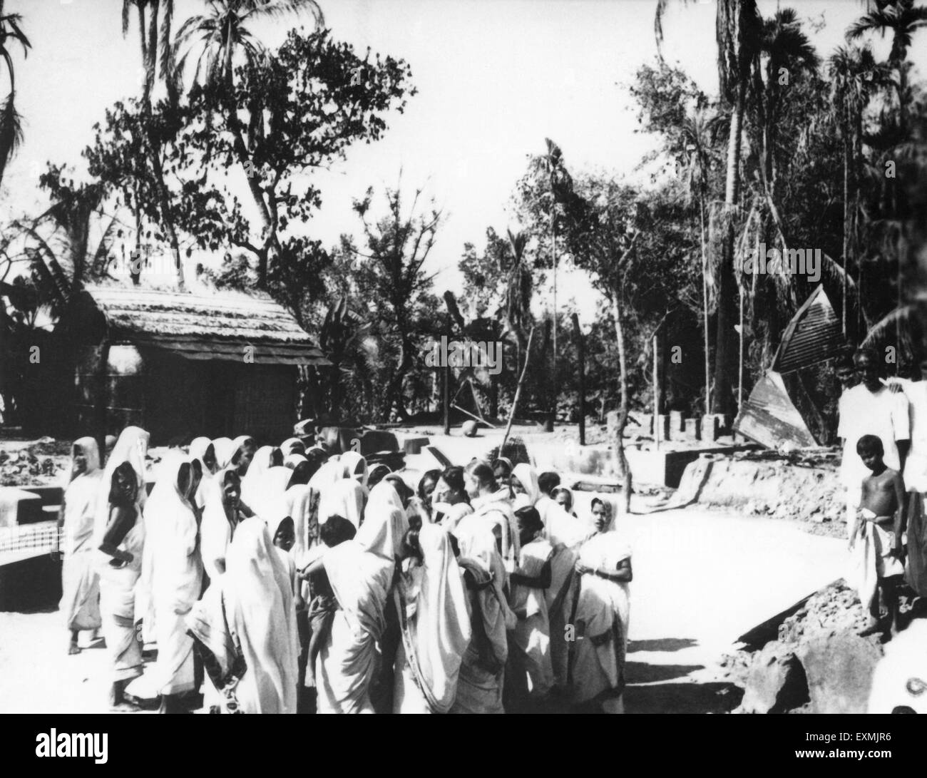 A group of crying women waiting to meet Mahatma Gandhi after the riots between Hindus and Muslims in Noakhali East - Stock Image